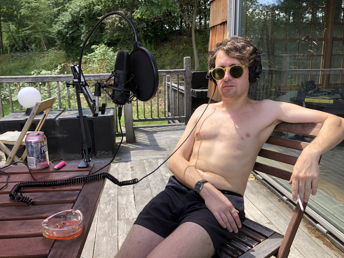 A shirtless Thomas Morton recording an episode of The Modernist Society